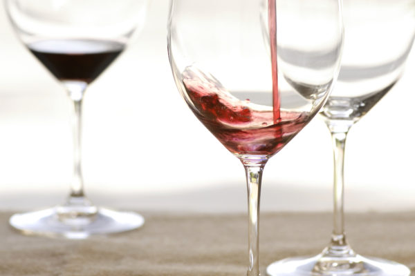 Three wine glasses with red wine pour in front.  Clean background with glasses placed on table.