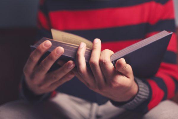 Closeup on a man reading a big heavy book